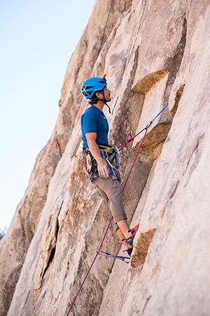 homme suspendu sur une falaise d'escalade