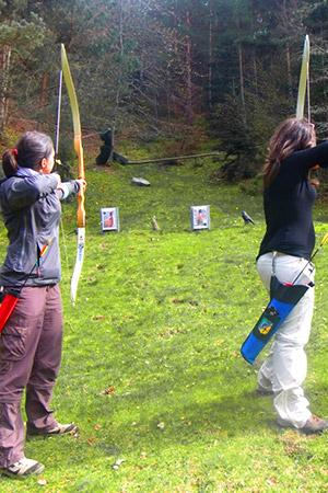 jeunes femmes tirant à l'arc sur des cibles en forme d'animaux dans la forêt
